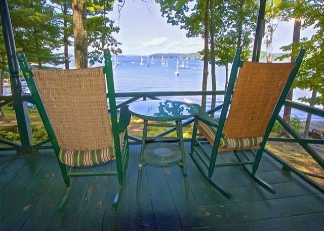Patio chairs looking out on a lake.