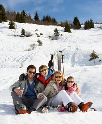 A portrait of a happy family at the bottom of a slope during their ski trip in New Hampshire.