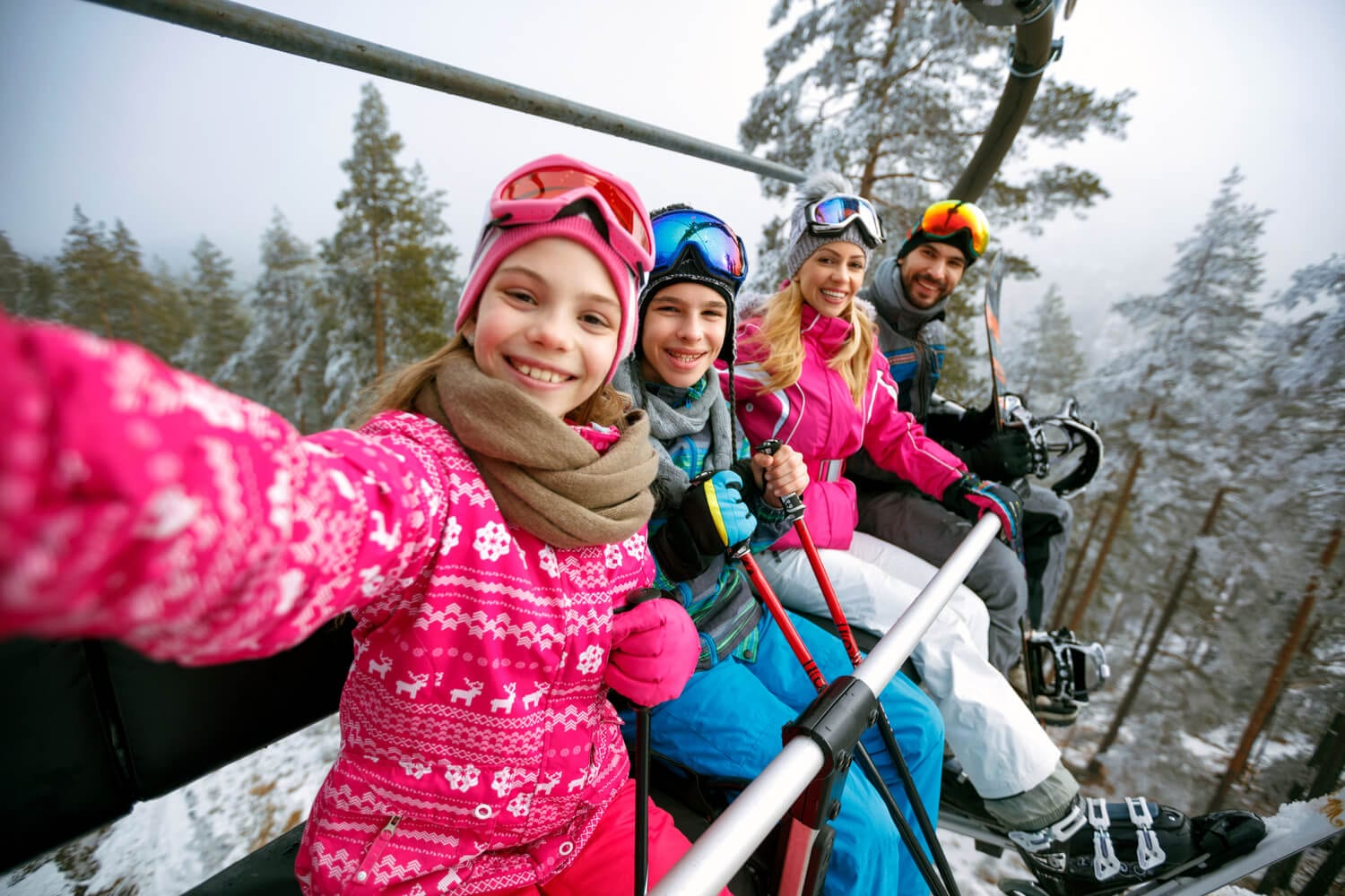A happy family takes a selfie on a lift while skiing in New Hampshire.