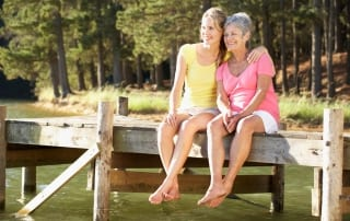 An elderly mother and her adult daughter share a joyous moment while admiring the view at their New Hampshire lake vacation rental.