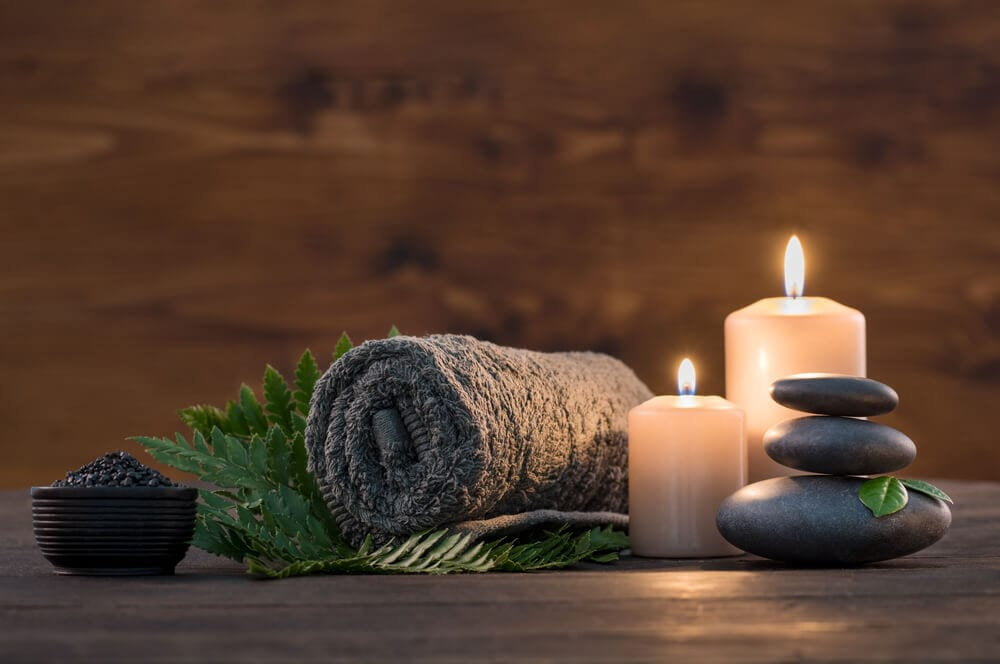 Grey towel nestled in between spa candles and spa rocks.