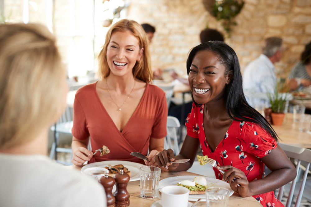 A group of friends enjoy the best brunch in New Hamsphire, smiling over their food and drinks.