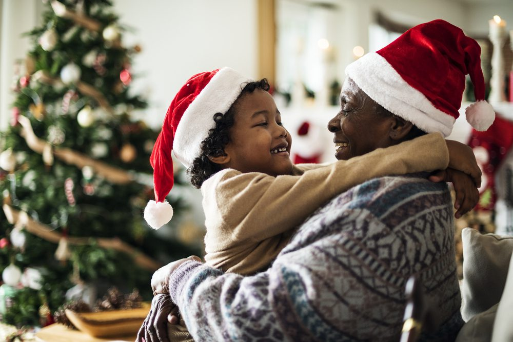 A grandfather holds his grandson, as they wear Santa hats during their Christmas getaway in New Hampshire, with Bayside Rentals.
